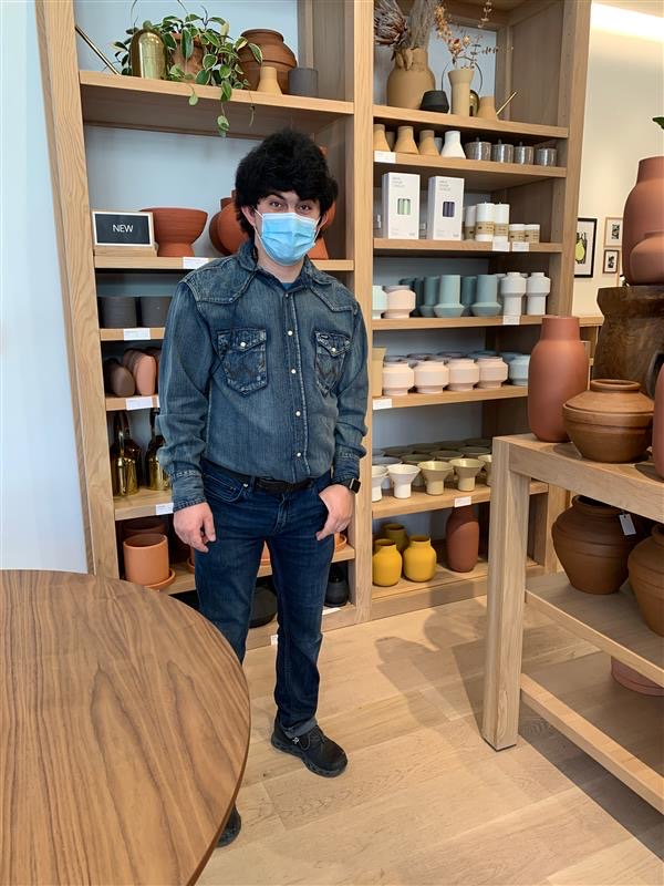 Young man in face mask standing in housing goods retail store.
