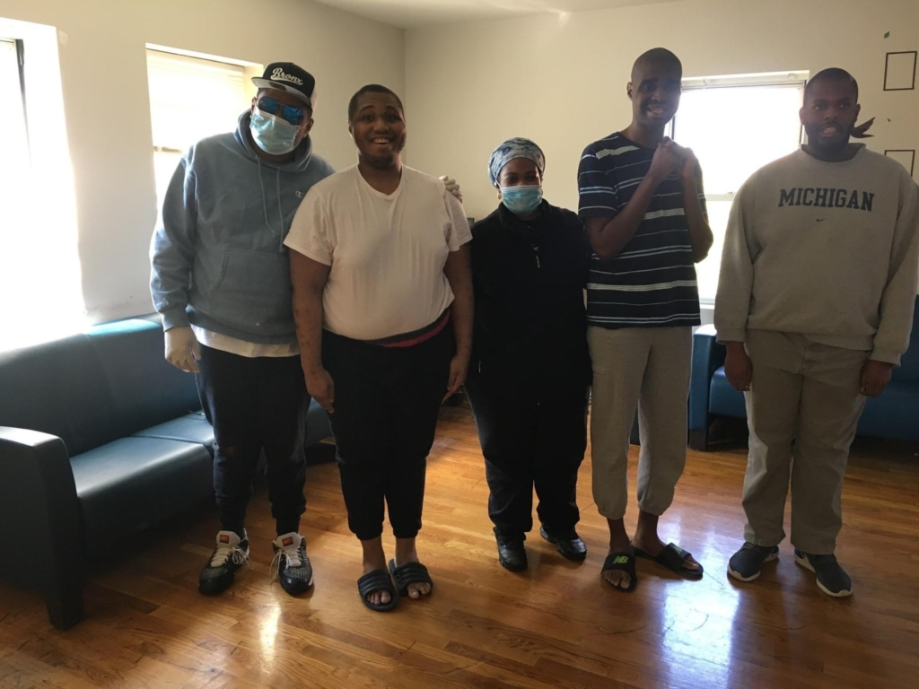 Nurse wearing a mask standing with people she supports at Birch's 52nd Street Residence