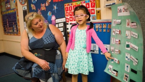 Pre-school girl in glasses standing at an activity board while teacher looks on.